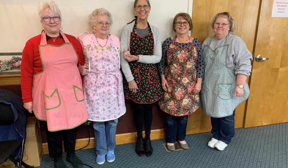 Teaching how to make aprons is one way Master Clothing Volunteers give back.